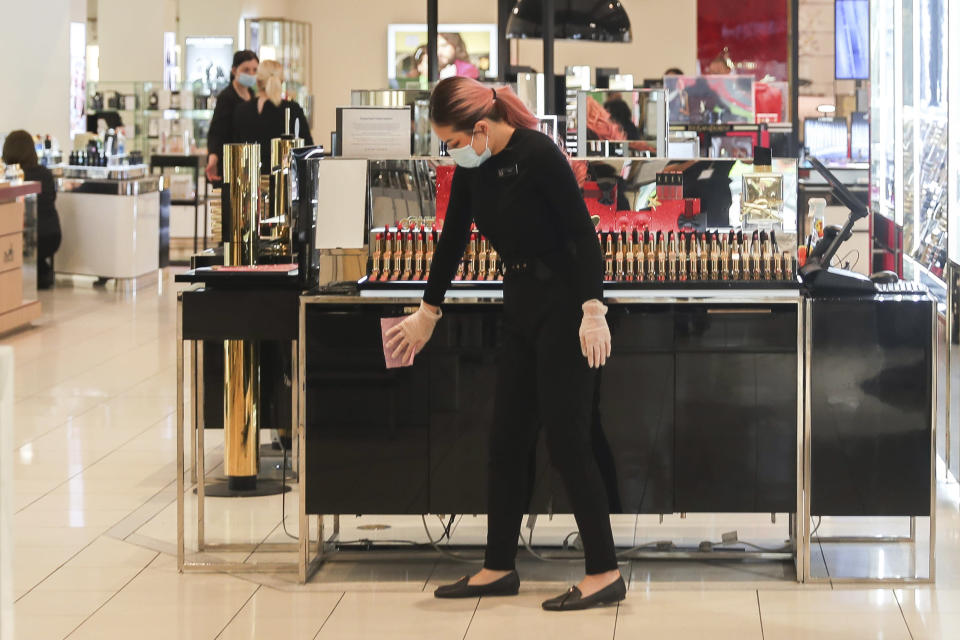 A worker inside a retail department store wipes down a cosmetics display shelf in Melbourne, Australia, Wednesday, Oct. 28, 2020. Australia's second largest city of Melbourne which was a coronavirus hotspot emerges from a nearly four-months lockdown, with restaurants, cafes and bars opening and outdoor contact sports resuming on Wednesday. (AP Photo/Asanka Brendon Ratnayake)