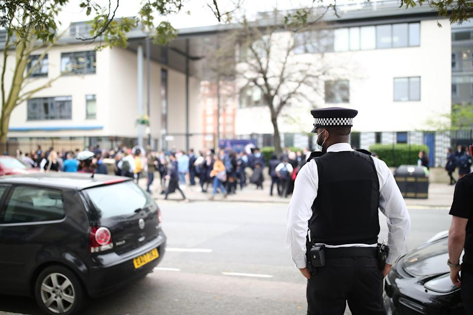 <p>A police officer outside Pimlico School where pupils protested against Mr Smith's uniform policies</p> (PA)