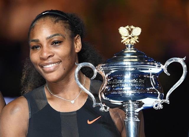 Serena Williams holds the trophy following her victory over sister Venus in the Australian Open final, in Melbourne, on January 28, 2017 (AFP Photo/PAUL CROCK )