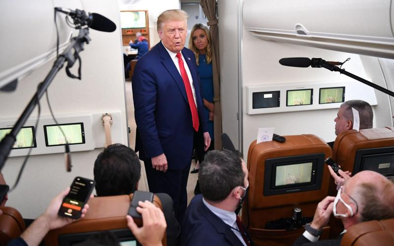 US President Donald Trump, flanked by White House Press Secretary Kayleigh McEnany, speaks to reporters onboard Air Force One - AFP