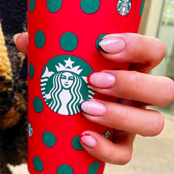 """Add a little Christmas spirit to <a href=""""https://www.glamour.com/story/french-manicure-ideas?mbid=synd_yahoo_rss"""" rel=""""nofollow noopener"""" target=""""_blank"""" data-ylk=""""slk:2020's coolest nail trend"""" class=""""link rapid-noclick-resp"""">2020's coolest nail trend</a> with red and green tips. Bonus points if you match your coffee cup."""
