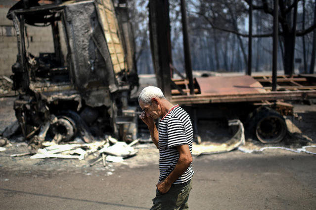 <p>A man walks past the remains of his truck, which was destroyed during a forest fire in Figueiro dos Vinhos, Portugal, June 18, 2017. (Patricia De Melo Moreira/AFP/Getty Images) </p>