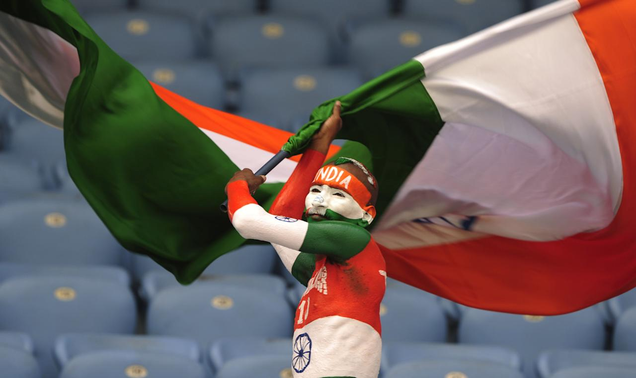 TOPSHOTS An Indian supporter waves a Indian national flag prior to the one day international (ODI) Asia Cup cricket match between India and Sri Lanka at the Sher-e-Bangla National Cricket Stadium in Dhaka on March 13, 2012. AFP PHOTO/Munir uz ZAMAN (Photo credit should read MUNIR UZ ZAMAN/AFP/Getty Images)
