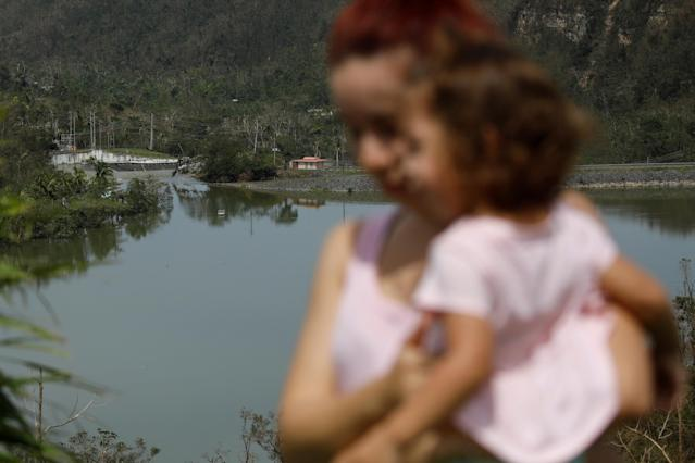 <p>Yadira Nieves carries her daughter as they look at water flowing over the road at the dam of the Guajataca lake after the area was hit by Hurricane Maria in Guajataca, Puerto Rico, Sept. 23, 2017. (Photo: Carlos Garcia Rawlins/Reuters) </p>