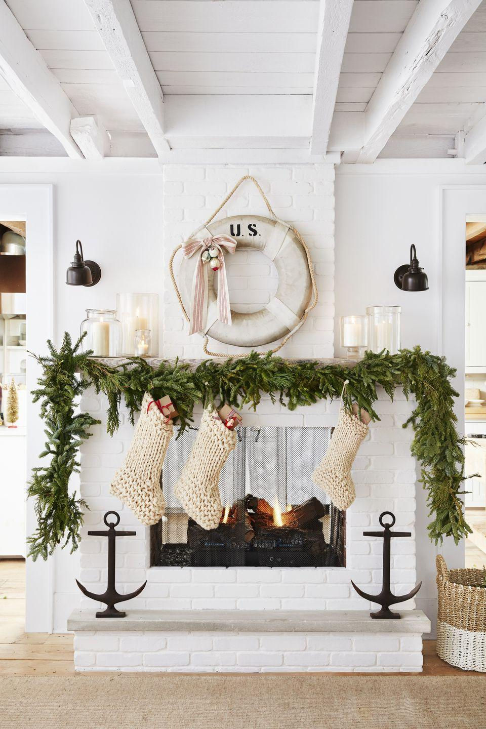 <p>A pair of sconces flanks this brick veneer fireplace to give it a warm holiday glow. The homeowner added a splash of nautical flair with an antique life preserver adorned with a festive bow. </p>