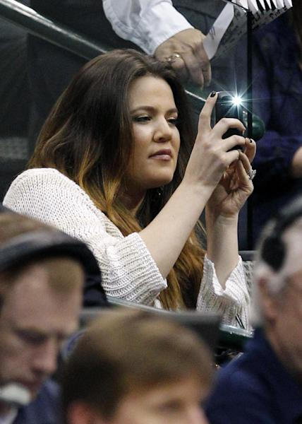 Khloe Kardashian, wife of Dallas Mavericks' Lamar Odom, uses a mobile phone to make a photo during the NBA basketball game against the Utah Jazz, Saturday, March 3, 2012, in Dallas. (AP Photo/LM Otero)