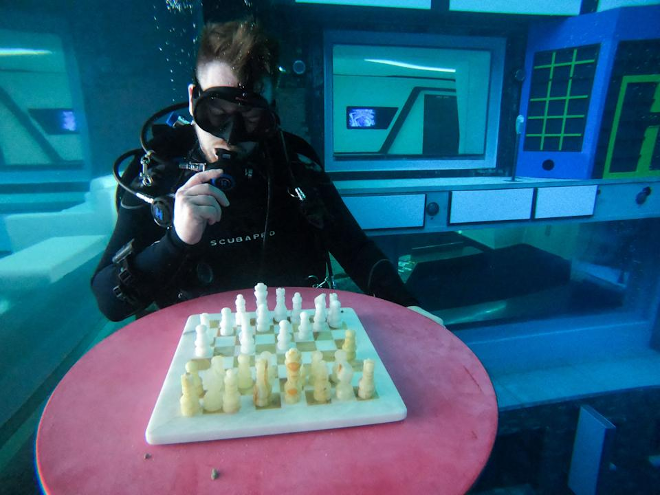 A diver plays mock chess as he experiences Deep Dive Dubai, the deepest swimming pool in the world reaching 60m, in the United Arab Emirates, on July 10, 2021. - The city of superlatives, with the world's tallest tower among its many records, Dubai now has the deepest swimming pool on the planet complete with a
