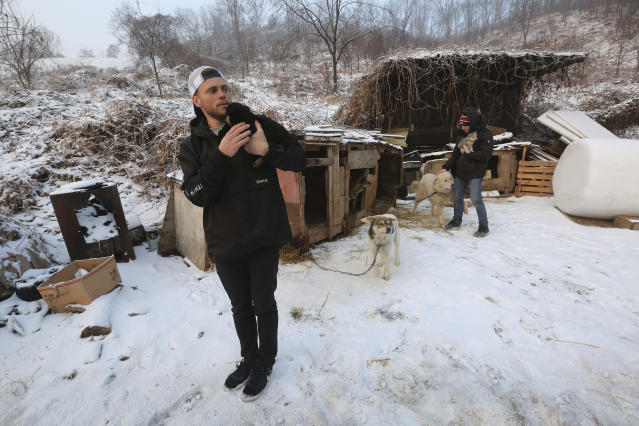 In this Friday, Feb. 23, 2018, photo, American freestyle skier Gus Kenworthy, left, and his boyfriend Matthew Wilkas visit a dog meat farm in Siheung, South Korea. Kenworthy saved five stray dogs during the Sochi Olympics four years ago and is considering adopting one of the many puppies he met Friday after finishing competition the Pyeongchang Games. (AP Photo/Ahn Young-joon)