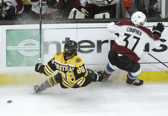 Boston Bruins's David Pastrnak, of Czech Republic, (88) and Colorado Avalanche's J.T. Compher (37) skate past the puck during the first period of an NHL hockey game, Sunday, Feb. 10, 2019, in Boston. (AP Photo/Steven Senne)