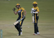 Peshawar Zalmi Haider Ali, left, celebrates after playing winning score while teammate Shoaib Malik watches during a Pakistan Super League T20 cricket match between Multan Sultans and Peshawar Zalmi at the National Stadium, in Karachi, Pakistan, Tuesday, Feb. 23, 2021. (AP Photo/Fareed Khan)