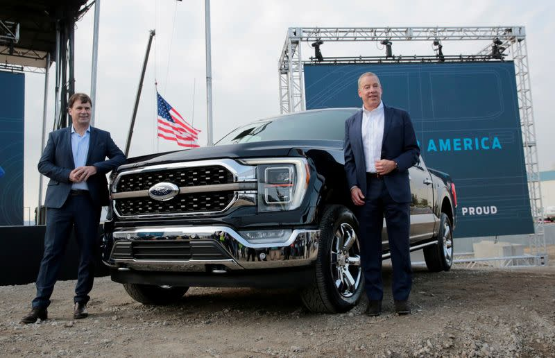 FILE PHOTO: Ford Motor Co. CEO Jim Farley and Executive Chairman Bill Ford Jr. pose next to a new 2021 Ford F-150 pickup truck in Dearborn, Michigan