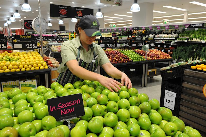 An employee arranges apples in the fruit and vegetable inside a Woolworths grocery store in Brisbane.