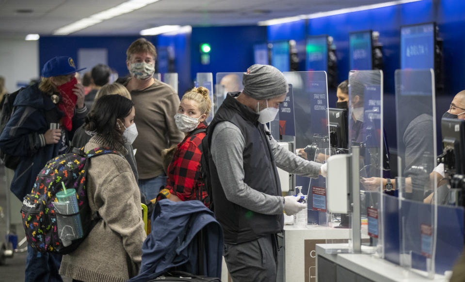Travellers wearing masks get their tickets and check luggage at LAX.