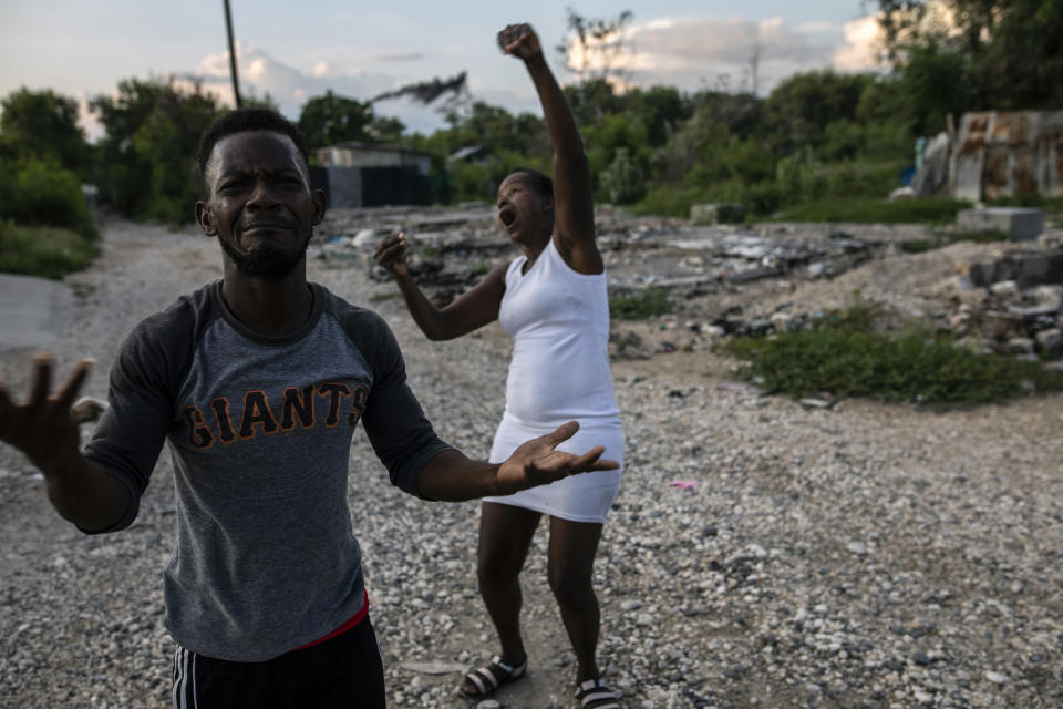 Felix Gelin and Claudine Jean describe in sign language how their community, the La Piste encampment, went up in flames this past summer, in Port-au-Prince, Haiti, Sunday, Sept. 20, 2021. According to residents and a United Nations account, police lead the assault at dusk on the encampment, a shelter for deaf and disabled Haitians relocated there by the International Red Cross after the 2010 earthquake leveled the capital. (AP Photo/Rodrigo Abd)