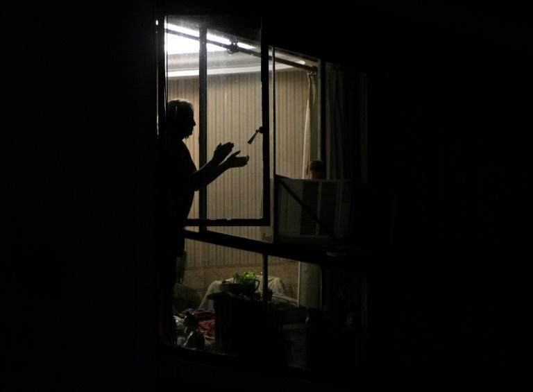 """A woman in Buenos Aires, Argentina claps her hands to express gratitude to health workers, a nightly tradition during the """"preventative and compulsory"""" lockdown"""
