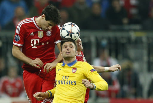 Arsenal's Oliver Giroud, front, and Bayern's Javier Martinez, left, and Bastian Schweinsteiger go for a header during the Champions League round of 16 second leg soccer match between FC Bayern Munich and FC Arsenal in Munich, Germany, Wednesday, March 12, 2014. (AP Photo/Matthias Schrader)