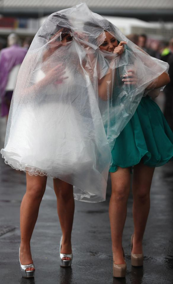 LIVERPOOL, ENGLAND - APRIL 13:  Racegoers brave the rain as they refuse to let it spoil the occasion of Ladies Day at the Aintree Grand National meeting on April 13, 2012 in Aintree, England. Friday is traditionally Ladies day at the three-day meeting of the world famous Grand National, where fashion and dressing to impress is as important as the racing.  (Photo by Christopher Furlong/Getty Images)