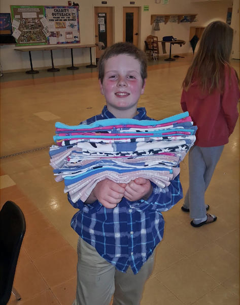 This Jan. 12, 2020 photo provided by Meg Hydock shows Gibson Griffith, 10, holding a stack of fabric crate liners he and others sewed to send to wildlife injured in wildfires in Australia in Lee, N.H. Griffith, who organized a sewing party is among thousands of people worldwide who have been making everything from bat wraps to kangaroo joey pouches for the animals affected by the wildfires. (Meg Hydock via AP)