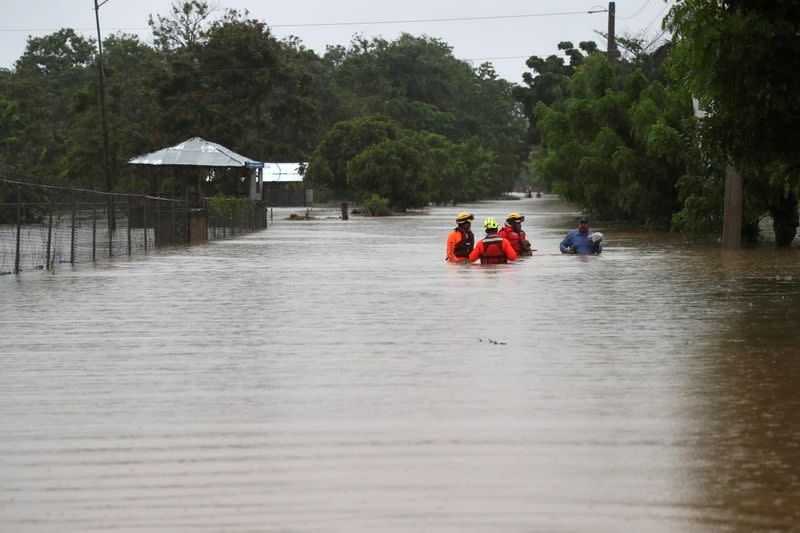 Rescue workers are seen on a flooded street, after Storm Laura passed through Santo Domingo