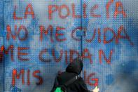 """A woman writes """"Police don't take care of me"""" on a wall during a demonstration in the Mexican capital"""