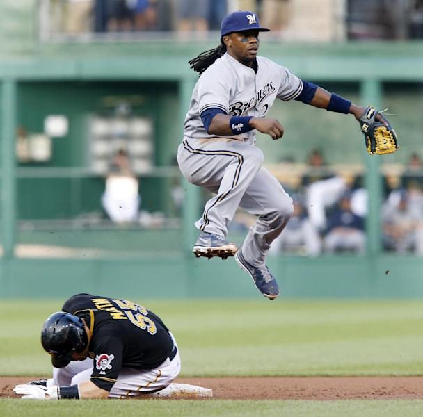 Milwaukee Brewers second baseman Rickie Weeks, top, hops over Pittsburgh Pirates' Russell Martin, watching his throw that completed a double play on Pedro Alvarez in the first inning of the baseball game on Saturday, June 29, 2013, in Pittsburgh. (AP Photo/Keith Srakocic)