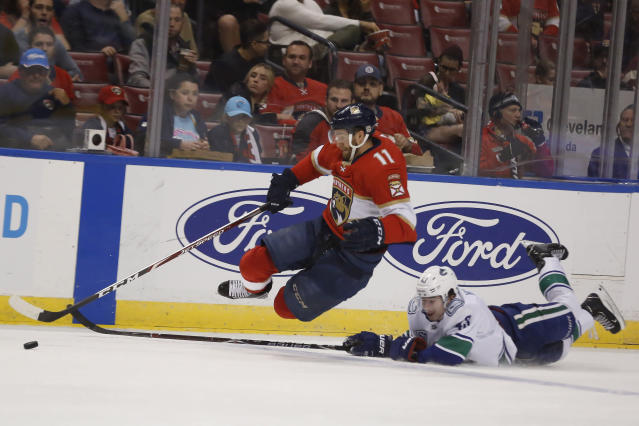 Florida Panthers left wing Jonathan Huberdeau (11) jumps after the puck against Vancouver Canucks defenseman Quinn Hughes (43) during the second period of an NHL hockey game Thursday, Jan. 9, 2020, in Sunrise, Fla. (AP Photo/Brynn Anderson)