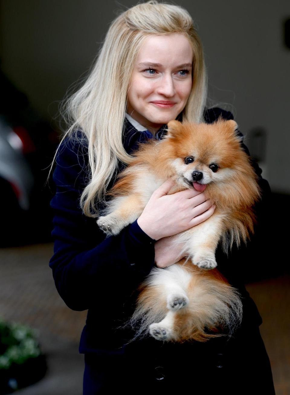 <p>Julia Garner cuddles up to a Pomeranian on the set of upcoming TV miniseries <i>Inventing Anna</i> on Tuesday in N.Y.C. </p>