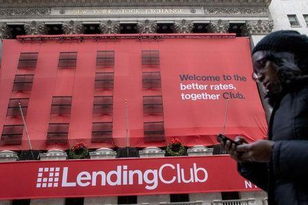 A woman looks at her phone as she passes by a Lending Club banner on the facade of the the New York Stock Exchange