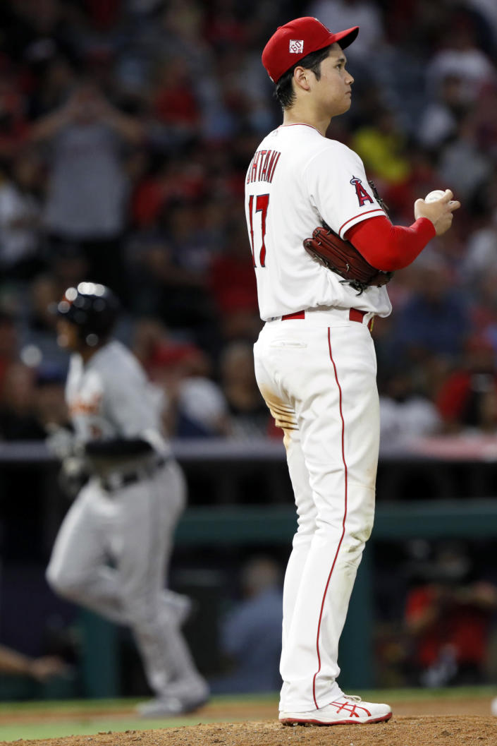 Los Angeles Angels staring pitcher Shohei Ohtani waits Detroit Tigers' Jonathan Schoop rounds third after hitting a solo home run during the sixth inning of a baseball game in Anaheim, Calif., Thursday, June 17, 2021. (AP Photo/Alex Gallardo)