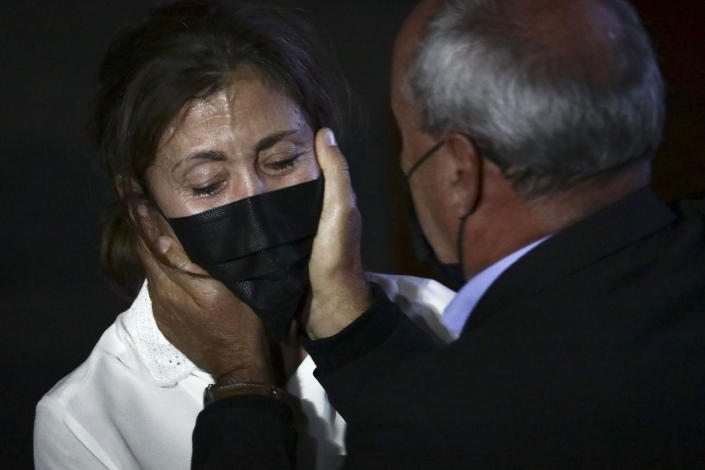 Former Colombian Presidential candidate Ingrid Betancourt, left, who was abducted while campaigning by the Revolutionary Armed Forces of Colombia, FARC, rebels, is comforted by another kidnapping victim during an event at the Truth Commission to commemorate victims of the country's decades long armed conflict, in Bogota, Colombia, Wednesday, June 23, 2021. (AP Photo/Ivan Valencia)