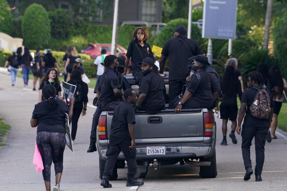 Members of the New Black Panther Party follow behind demonstrators, Thursday, May 27, 2021, in Baton Rouge, La., marching in protest to the death of Ronald Greene, who died in the custody of Louisiana State Police in 2019,. (AP Photo/Gerald Herbert)