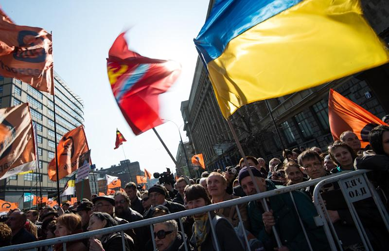 Russian opposition activists hold they party flags and a Ukrainan flag (right) as they rally in support of freedom of press in central Moscow, on April 13, 2014 (AFP Photo/Anatoly Tanin)