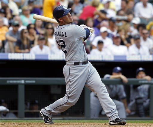 San Diego Padres' Yasmani Grandal follows the flight of his solo home run off Colorado Rockies starting pitcher Christian Friedrich in the fourth inning of the Padres' 8-4 victory in a baseball game in Denver on Saturday, June 30, 2012. (AP Photo/David Zalubowski)