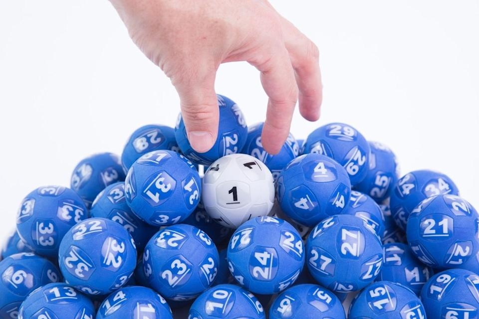A hand chooses a number out of a pile of numbered Powerball balls. Source: The Lott