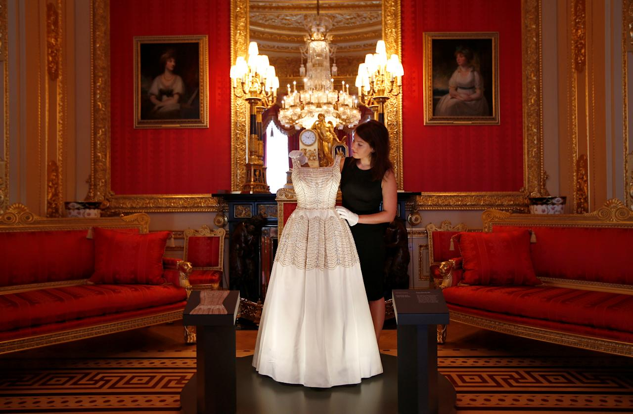 EMBARGOED UNTIL 23:01 GMT SEPTEMBER 15, 2016. A member of staff of the Royal Collection poses with a dress worn by Britain's Queen Elizabeth, in the Crimson Drawing Room at Windsor Castle in Windsor, Britain September 15, 2016. The exhibition Fashioning a Reign: 90 Years of Style from The Queen's Wardrobe, will show at the castle from September 17, 2016 to January 8, 2017.  REUTERS/Peter Nicholls     TPX IMAGES OF THE DAY