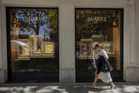 A woman walks past a jewelry store in the upmarket neighborhood of Salamanca in Madrid, Spain, Monday, Sept. 28, 2020. The extended region around Madrid, comprising a population of 6.6 million, is struggling to control coronavirus outbreaks. Heightened restrictions in some of Madrid's working-class neighborhoods brought a heated debate over the prevalence of inequality in Spain. (AP Photo/Bernat Armangue)