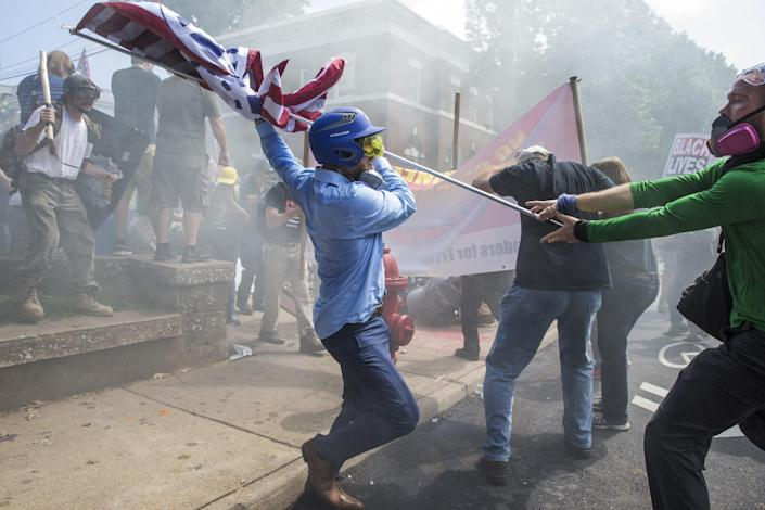 <p>A White Supremacist tries to strike a counter protestor with a White Nationalist flag during clashes at Emancipation Park where the White Nationalists are protesting the removal of the Robert E. Lee monument in Charlottesville, Va., on Aug. 12, 2017. (Photo: Samuel Corum/Anadolu Agency/Getty Images) </p>