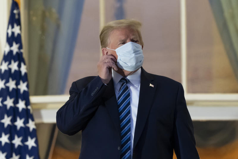 President Donald Trump removes his mask as he stands on the Blue Room Balcony upon returning to the White House Monday, Oct. 5, 2020, in Washington, after leaving Walter Reed National Military Medical Center, in Bethesda, Md. Trump announced he tested positive for COVID-19 on Oct. 2. (AP Photo/Alex Brandon)