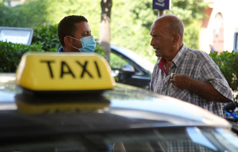 Zakaria Ghalayeeni, 76-year-old Lebanese taxi driver, talks to a worker at a gas station in Beirut