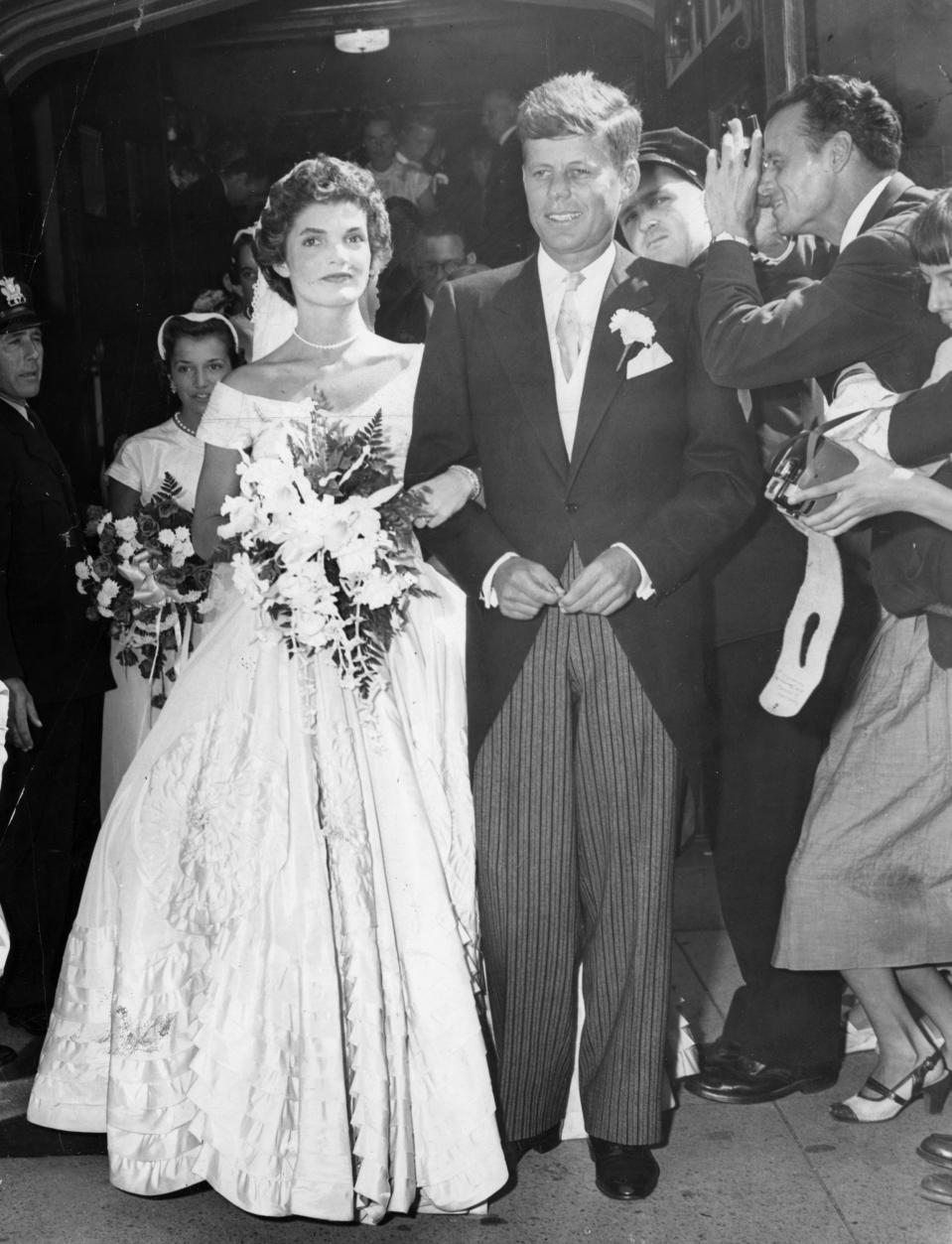 NEWPORT, RI - SEPTEMBER 12: Jackie Kennedy and John F. Kennedy walk out of St. Mary's Church in Newport, R.I. after their wedding ceremony, Sept. 12, 1953.  (Photo by Charles McCormick /The Boston Globe via Getty Images)