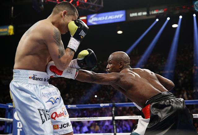 Floyd Mayweather Jr., right, reaches with a left to the body of Marcos Maidana, from Argentina, in their WBC-WBA welterweight title boxing fight Saturday, May 3, 2014, in Las Vegas. (AP Photo/Eric Jamison)