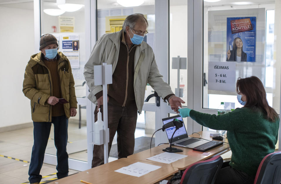 Lithuanian's, wearing face masks to protect against coronavirus, arrive to cast their ballots at a polling station during the second round of a parliamentary election in Vilnius, Lithuania, Sunday, Oct. 25, 2020. Polls opened Sunday for the run-off of national election in Lithuania, where the vote is expected to bring about a change of government following the first round, held on Oct. 11, which gave the three opposition, center-right parties a combined lead. (AP Photo/Mindaugas Kulbis)