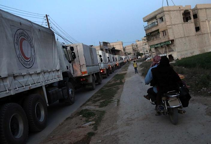 A Syrian family drives on a scooter alongside Syrian Arab Red Crescent lorries carrying aid as they arrive in the town of Saqba (AFP Photo/Amer Almohibany)
