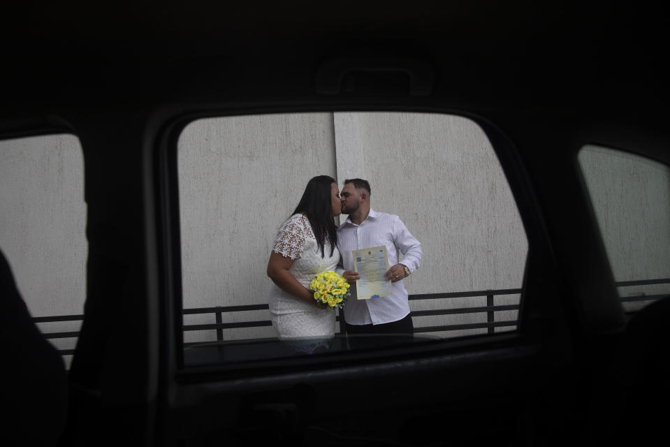 Ayrton, right, and Natasha, kiss after their drive-thru wedding at the registry office in the neighborhood of Santa Cruz in Rio de Janeiro, Brazil, Thursday, May 28, 2020. Couples unable to have a traditional wedding because of the coronavirus pandemic are now taking part in drive-thru weddings. (AP Photo/Silvia Izquierdo)