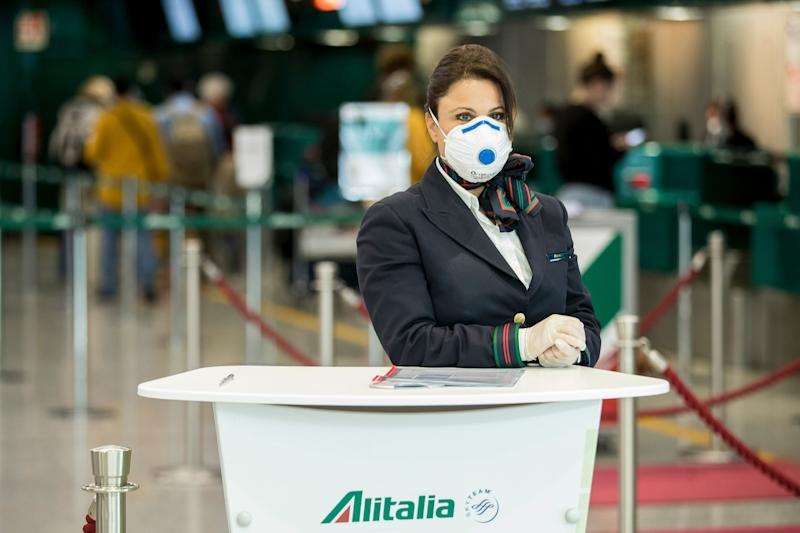 An Alitalia employee waits at the desk the Leonardo Da Vinci airport, in Rome, Tuesday, March 17, 2020. For most people, the new coronavirus causes only mild or moderate symptoms. For some it can cause more severe illness, especially in older adults and people with existing health problems.(Roberto Monaldo/LaPresse via AP)