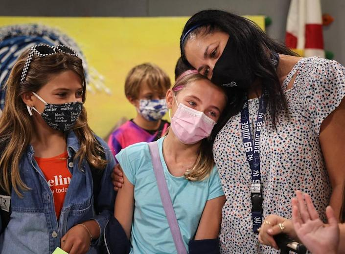 Fourth-grader Lilly Williams, 10, center, tears up while saying goodbye to her iPrep Academy teacher, Elizabeth Martinez, right, for the summer. Superintendent Alberto Carvalho recapped all the challenges of the school year on Wednesday, June 9, 2021, the last day of school for Miami-Dade Schools students.