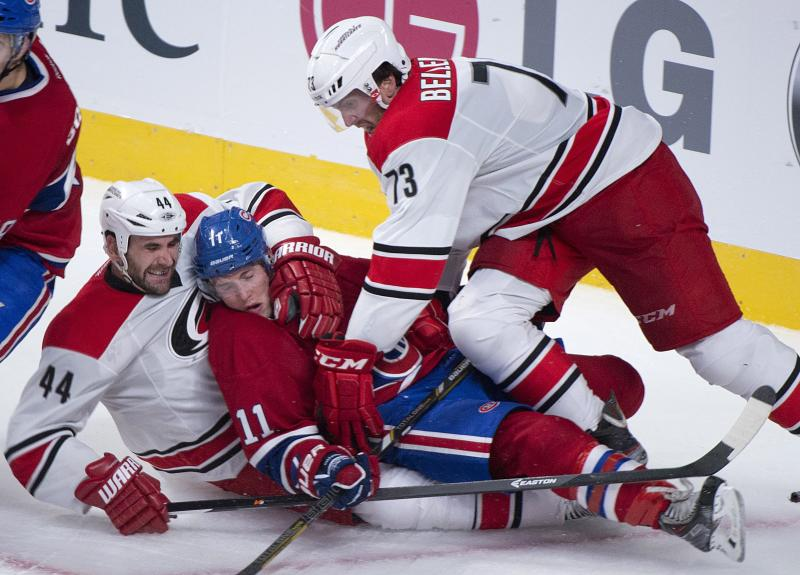 Montreal Canadiens' Brendan Gallaghers, center, is sandwiched between Carolina Hurricanes' Jay Harrison, left, and Brett Bellemore during the second period of an NHL hockey preseason game in Montreal, Saturday, Sept. 21, 2013. (AP Photo/The Canadian Press, Graham Hughes)