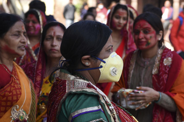 A reveller wearing a facemask amid fears of the spread of COVID-19 novel coronavirus, arrives to celebrate Holi, the spring festival of colours, on March 9, 2020. - Holi is observed at the end of the winter season on the last full moon of the lunar month. (Photo by PRAKASH MATHEMA / AFP) (Photo by PRAKASH MATHEMA/AFP via Getty Images)
