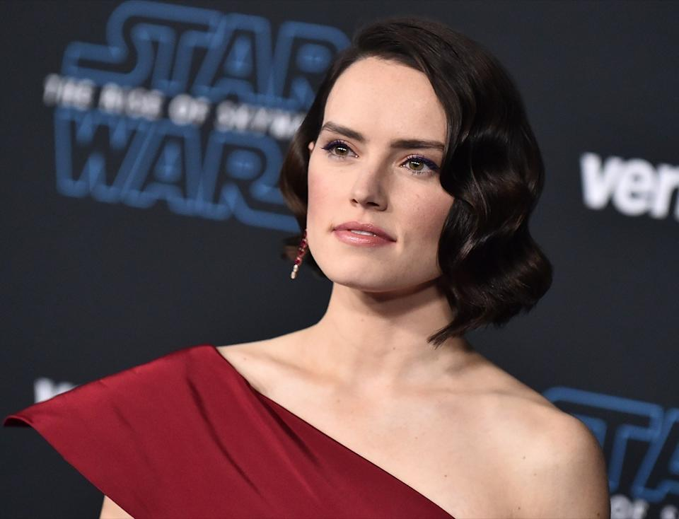 "Daisy Ridley wears a red dress as the premiere of ""Star Wars: The Rise of Skywalker"" in 2019"