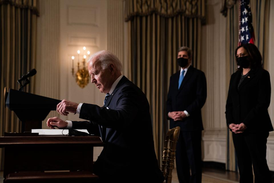 WASHINGTON, DC - JANUARY 27: U.S. President Joe Biden prepares to sign executive orders after speaking about climate change issues in the State Dining Room of the White House on January 27, 2021 in Washington, DC. President Biden signed several executive orders related to the climate change crisis on Wednesday, including one directing a pause on new oil and natural gas leases on public lands. Also pictured, left to right, Special Presidential Envoy for Climate John Kerry and U.S. Vice President Kamala Harris. (Photo by Anna Moneymaker-Pool/Getty Images)